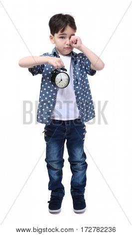 Cute little boy with alarm clock on white background