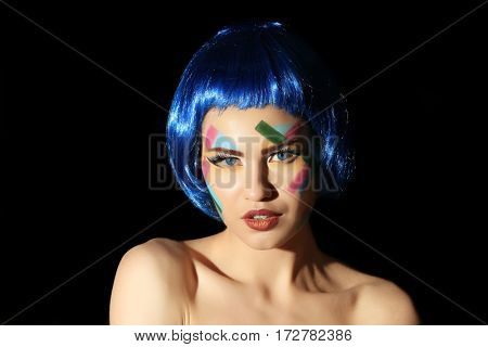 Portrait of young woman with creative make up and blue hair on black background