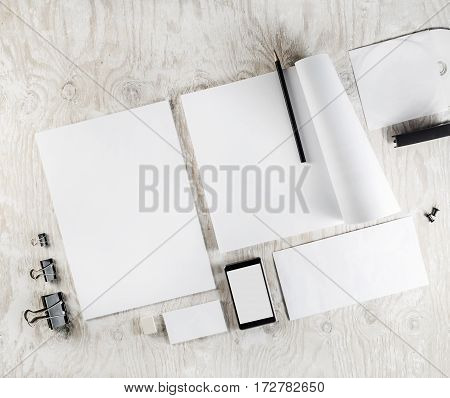 Blank corporate identity template on light wooden table background. Photo of blank stationery ID mock-up. Mockup for branding identity. Blank objects for placing your design. Responsive design mock up.Top view.