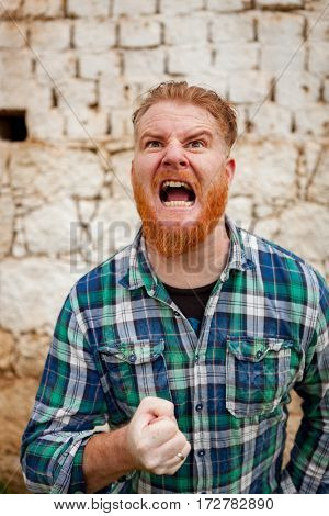 Portrait of red haired hipster man with blue plaid shirt expressing a emotion
