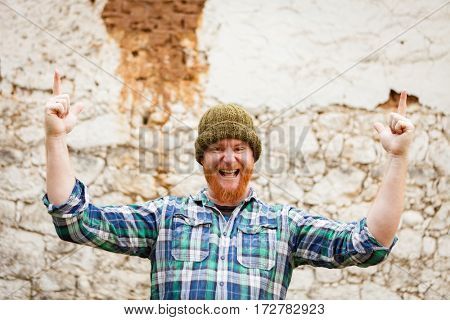Red haired man with plaid shirt celebrating something