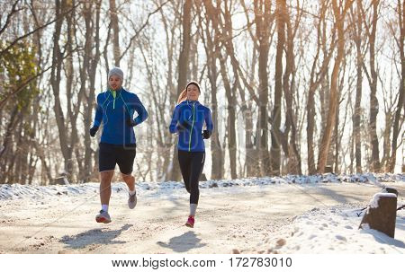 Young couple in condition running in forest
