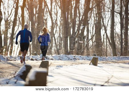 Couple running on condition  training in nature, back view