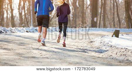 Young couple running in forest, back view
