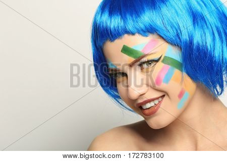 Face of young woman with creative make up and blue hair on light background