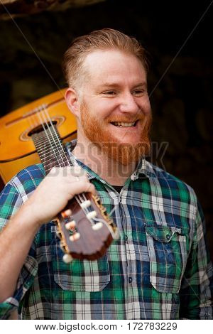 Hipster man with red beard holding a guitar in a rustic house