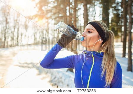 Female drinks water on break from running in forest