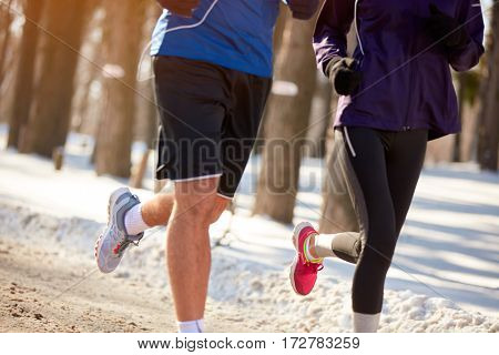 Legs of runners couple while runs, concept