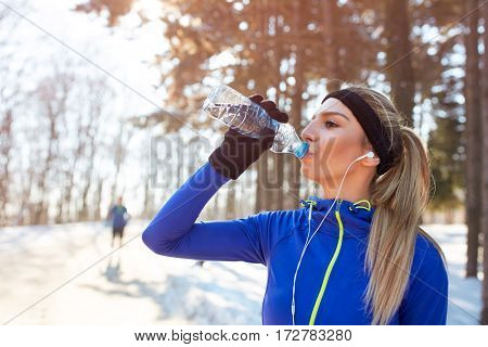 Girl drinks water on winter training outdoor