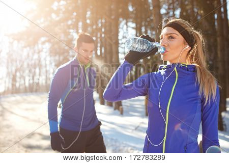 Thirsty girl drinks water on training in winter in forest