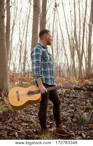 Pensive hipster man with red beard holding a guitar in the forest