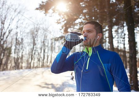 Thirsty male athlete drinking water after running outdoor