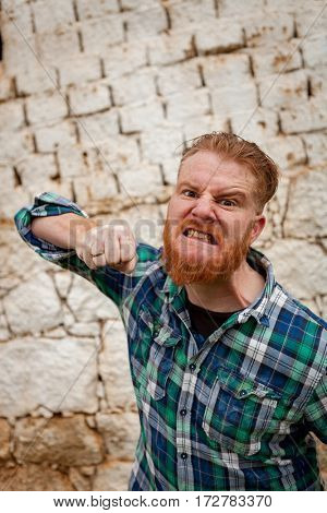 Angry red haired hipster man with blue plaid shirt