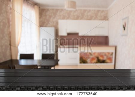 Blurred and abstract background. Empty wooden tabletop and defocused modern kitchen background for display or montage your products.
