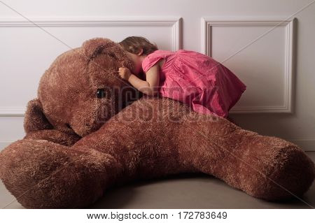 horizontal front view of a little Caucasian girl with short hair and a pink dress whispering to the ear of a large brown teddy bear on a floor against a white wall