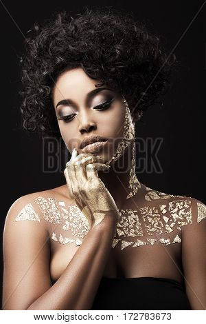 Beautiful Afro-American girl with curly hair in black dress. Make-up, hairdo. Covered with golden patterns. Looking down, fingers touching face. Waist up, indoors, studio