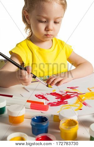 Cute little toddler child is painting in art school. Adorable baby girl sitting behind table and starts to paint, isolated on white background. Fresh fruits is on the table.
