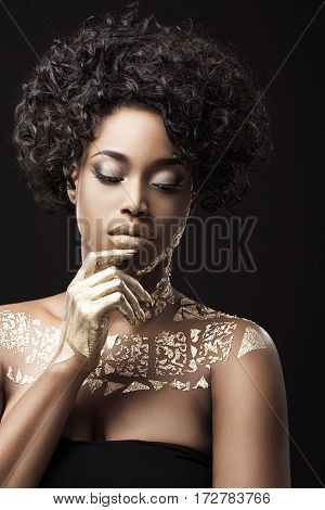Beautiful Afro-American girl with curly hair in black dress. Make-up, hairdo. Covered with golden patterns. Looking down, finger touching lower lip. Waist up, indoors, studio