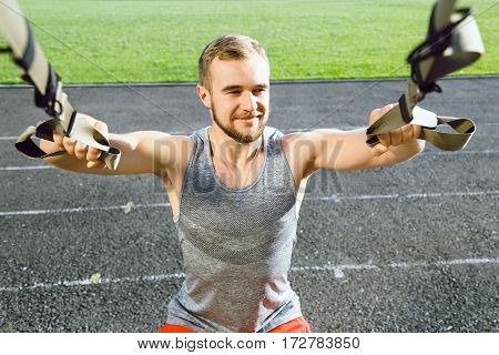 Fit man wearing dark sport T-shirt doing exercises with training loop equipment at stadium background, portrait, arms workout.