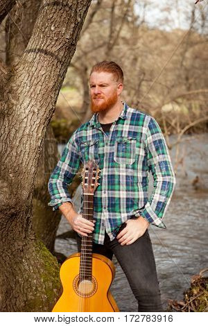 Hipster man with red beard with a guitar in the field