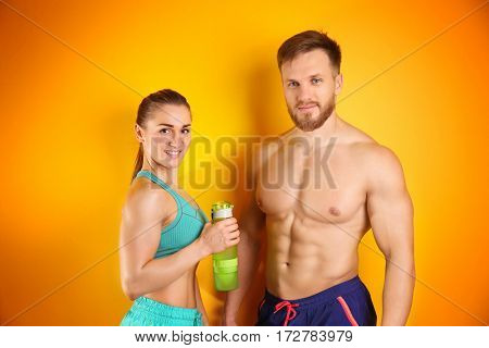 Sporty young couple with bottle of water on color background