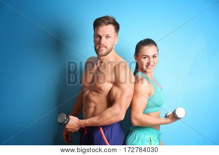 Sporty young couple with dumbbells on color background