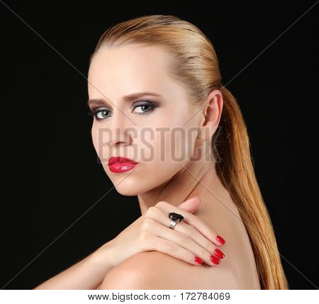 Portrait of beautiful young woman with fashionable ring on black background