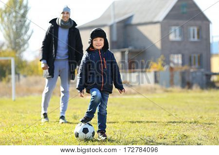 Father and son playing football on soccer pitch