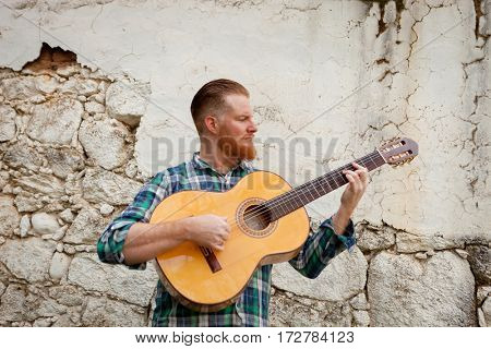 Hipster man with red beard playing a guitar with a old wall of background