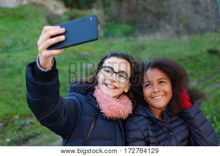 Two girls taking a photo with the mobile in the park.
