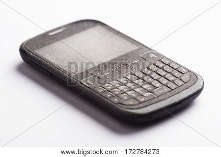 Side view close up of old black smartphone mobile with qwerty keyboard covered in dust and isolated on white background