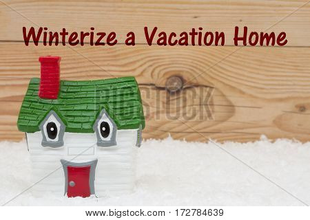 Your vacation house in the winter season A green and red house on snow and a weathered wood background with text Winterize a Vacation Home