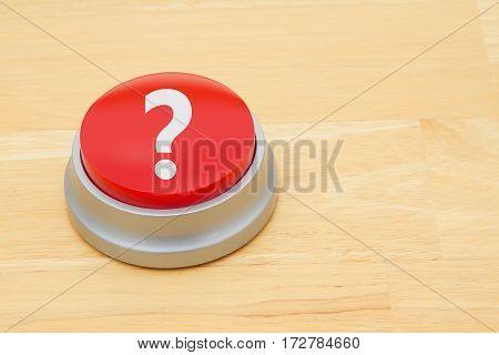 A Question Mark red push button A red and silver push button on a wooden desk with text Question Mark