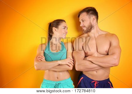 Sporty young couple on color background