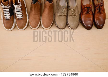 Row of Men's boots , leather brown shoes on wooden background