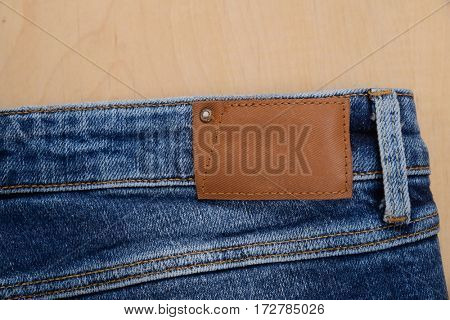 jeans pants with back pocket and brown leather tag- wooden background