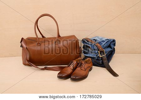 Men's shoes, bag, jeans with accessories on wooden background
