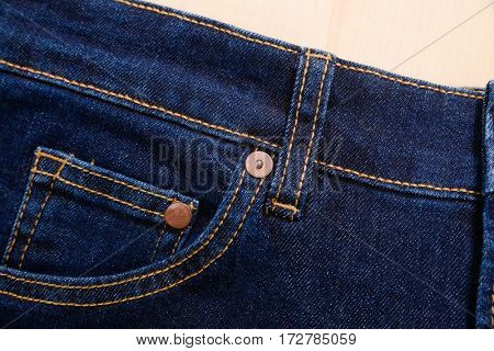Close up,Blue Jeans texture-wooden background