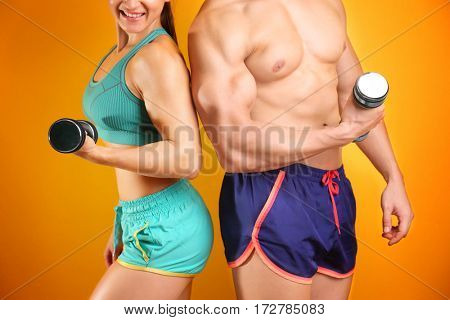 Sporty young couple with dumbbells on color background, closeup