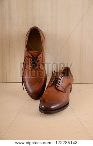 male leather brown shoes on wooden background