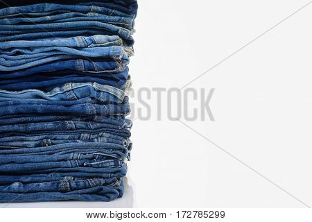 Jeans stacked on a white background