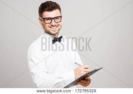 Man with black hair and beard wearing white shirt with bowtie and glasses writing notes at gray studio background, portrait, smiling.