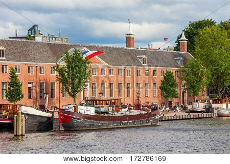 Big boat on canal in front of red brick building in Amsterdam, Netherlands.