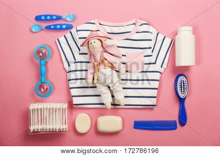 Baby clothes and necessities on pink background