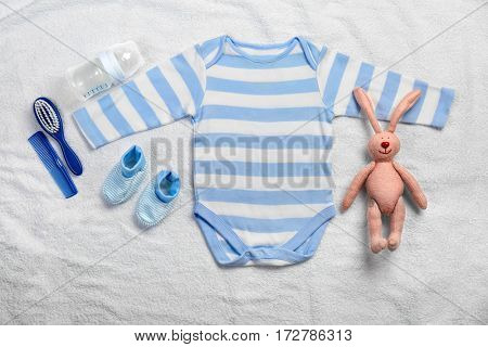Baby clothes and necessities on white towel background