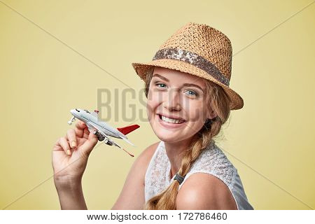 Closeup portrait of happy joyful beautiful woman in straw hat holding airplane model in hand