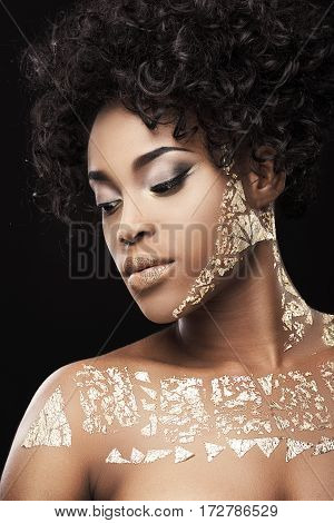 Portrait of beautiful Afro-American girl with curly hair. Make-up, hairdo. Covered with golden patterns. Looking aside and down. Head and shoulders, profile, indoors, studio