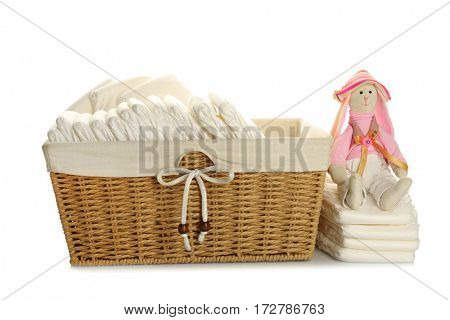 Baby diapers in wicker basket with toy, on white background