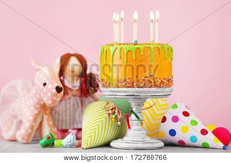 Delicious cake with happy birthday candles on festive blurred background