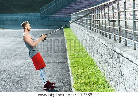 Fit man wearing dark sport T-shirt doing exercises with training loop equipment at stadium background, portrait.
